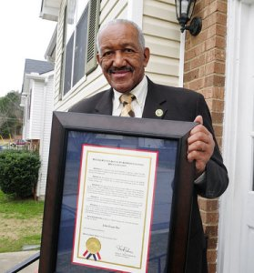 "John Evans holds a proclamation from the U.S. House of Representatives declaring October 27 as ""John Evans Day"" for his work as a community leader in DeKalb County. -Neighbor Newspaper Staff / Samantha M. Shal"